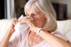 Stående av äldre kvinna som inomhus dricker te på soffan Arkivbilder