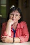 Stående av åldriga kvinnor som sitter på tabellen Tänka arkivbild