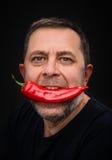Åldringen bemannar med röd peppar i hans mun Royaltyfri Foto