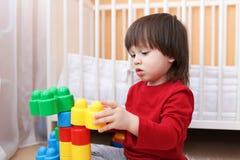Stående av 2 år litet barn som spelar plast- kvarter Arkivfoto