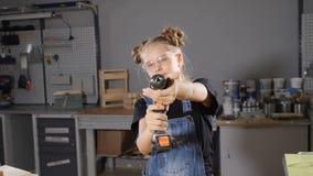 Stående av årig flicka 10 i träsnickeri som rymmer en elektronisk drillborr som poserar på kameran Litet byggmästarebegrepp HD stock video