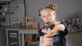 Stående av årig flicka 10 i träsnickeri som rymmer en elektronisk drillborr som poserar på kameran Litet byggmästarebegrepp HD arkivfilmer