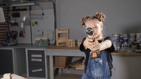 Stående av årig flicka 10 i träsnickeri som rymmer en elektronisk drillborr som poserar på kameran Litet byggmästarebegrepp HD lager videofilmer