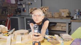 Stående av årig flicka roliga 10 i träsnickeri som rymmer en elektronisk drillborr som poserar på kameran byggmästare little lager videofilmer
