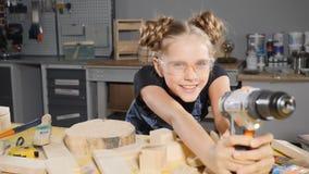 Stående av årig flicka roliga 10 i träsnickeri som rymmer en elektronisk drillborr som poserar på kameran byggmästare little arkivfilmer