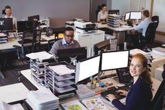 Stående av affärskvinnan med kollegor som arbetar på kontoret Arkivbilder