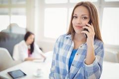 Stående av affärskvinnan som använder mobiltelefonen på det idérika kontoret Arkivbild