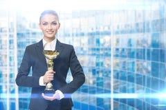 Stående av affärskvinnan som håller den guld- koppen arkivfoton