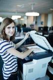 Stående av affärskvinnan som i regeringsställning använder kopieringsmaskinen Royaltyfri Bild