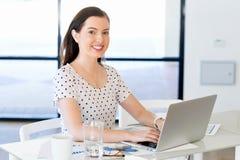Stående av affärskvinnan som i regeringsställning arbetar på datoren royaltyfria bilder