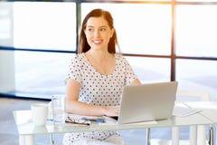 Stående av affärskvinnan som i regeringsställning arbetar på datoren royaltyfria foton