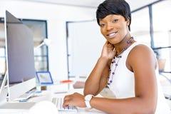 Stående av affärskvinnan som i regeringsställning arbetar på hennes skrivbord Arkivbilder