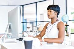 Stående av affärskvinnan som i regeringsställning arbetar på hennes skrivbord Royaltyfria Foton