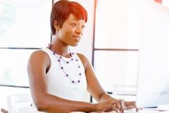Stående av affärskvinnan som i regeringsställning arbetar på hennes skrivbord Arkivfoton