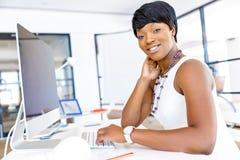 Stående av affärskvinnan som i regeringsställning arbetar på hennes skrivbord royaltyfri fotografi