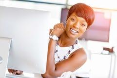 Stående av affärskvinnan som i regeringsställning arbetar på hennes skrivbord arkivfoto