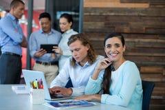 Stående av affärskvinnan som ler medan kollega som använder bärbara datorn Royaltyfri Bild