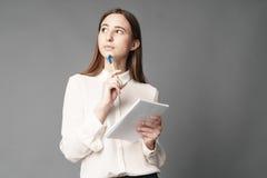 Stående av affärskvinnan som rymmer en anteckningsbok och en penna i hennes hand En isoleras på en grå bakgrund Royaltyfri Bild