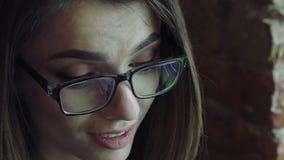 Stående av affärskvinnan som ser på en minnestavla och le lager videofilmer