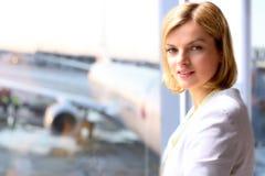 Stående av affärskvinnan som står det near fönstret Flygplanbakgrund bakom Royaltyfri Bild