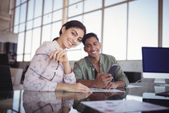 Stående av affärskvinnasammanträde med den manliga kollegan på kontoret arkivfoton