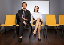 Stående av affärsman- och affärskvinnasammanträde i väntande rum royaltyfri bild