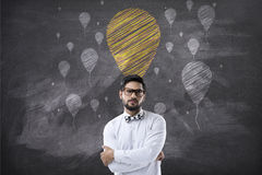 Stående av affärsmannen med korsade armar och kritaballongsymboler arkivfoton