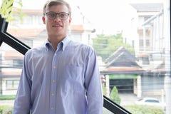 Stående av affärsmannen på kontoret leende för ung man på kameran Mor Arkivfoton