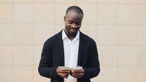 Stående av afrikansk amerikanaffärsmannen i dräkten som räknar pengaranseende nära kontorsmitt Honom fira som är hans stock video