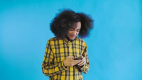 Stående av afrikansk amerikanmannen med lockigt hår som pratar på smartphonen på blå bakgrund Begrepp av sinnesr?relser arkivfilmer