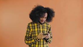 Stående av afrikansk amerikanmannen med lockigt hår som pratar på smartphonen på orange bakgrund Begrepp av sinnesr?relser lager videofilmer