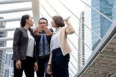 Stående av aggressiva unga asiatiska kvinnor i stridighet för formella kläder eller affärskvinna, medan mannen avråder för kamp royaltyfri bild
