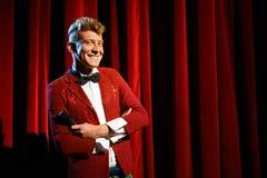 Stående av anchormanen på showen mot den röda gardinen Royaltyfri Bild