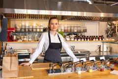 Stående av anseendet för ung kvinna bak diskbänken i liten eatery royaltyfri bild