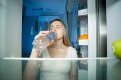Stående av anseendet för ung kvinna på det öppet kylskåpet och dricksvatten Begrepp av att banta och att lossa vikt royaltyfria bilder