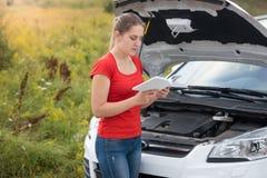 Stående av anseendet för ung kvinna på läsande manuell anvisning för bruten bil arkivbilder