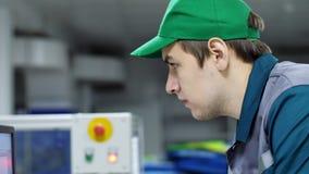 Stående av anställd av ett företag, fabrik en arbetare ser en datorbildskärm, justerar, kontrollerar arbetet av lager videofilmer