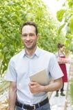 Stående av arbetsledaren med digitalt minnestavlaanseende mot bonde i växthus fotografering för bildbyråer