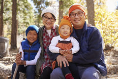 Stående av asiatföräldrar och två ungar i en skog Arkivbild