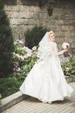 Stående av att bedöva bruden med långt hår som poserar med den stora buketten royaltyfria bilder
