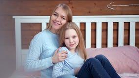Stående av att att bry sig den unga modern som kramar och poserar med den lilla dottern som ser kameran lager videofilmer