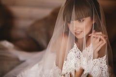 Stående av att charma bruden som sitter på sängen i ett hotellrum bruden täckas med skyler Br?llopmorgon arkivfoto