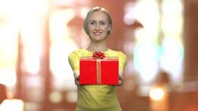Stående av att charma kvinnan som räcker gåvaasken lager videofilmer