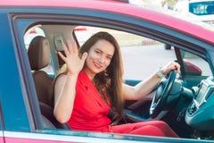 Stående av att le affärsdamen, caucasian chaufför för ung kvinna i den röda sommardräkten som ser kameran och avfärdar handstund arkivbild