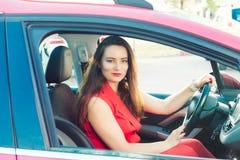 Stående av att le affärsdamen, caucasian chaufför för ung kvinna i den röda sommardräkten som ser kameran och ler, medan sitta arkivbilder