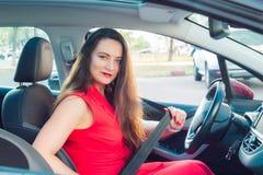 Stående av att le affärsdamen, caucasian chaufför för ung kvinna i den röda sommardräkten som ser kameran och sätter på hennes sä royaltyfri bild