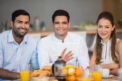 Stående av att le affärskollegor som har frukosten tillsammans royaltyfri fotografi