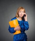 Stående av att le affärskvinnan med den pappers- mappen och smartphonen. Royaltyfria Bilder