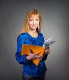 Stående av att le affärskvinnan med den pappers- mappen på grå bakgrund. Arkivfoto