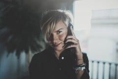 Stående av att le affärskvinnan som talar med partnern på smartphoneapparaten, medan arbeta avlägset i affärslopp royaltyfri fotografi